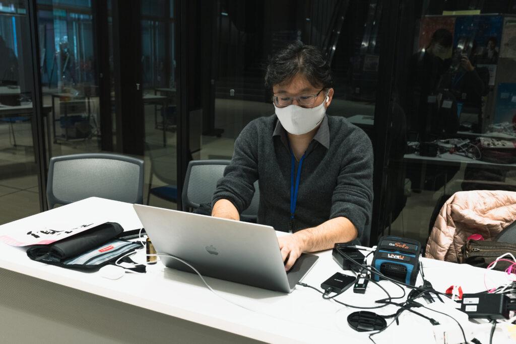 ホワイエでライブ配信管理をする岩崎将史